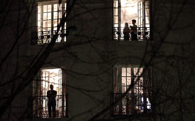 Des Parisiens applaudissent les travailleurs de santé depuis leur balcon à 20h, à Paris, le 18 mars 2020. (Crédit : THOMAS COEX / AFP)