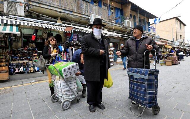 Un juif ultra-orthodoxe portant un masque au marché Mahane Yehuda de Jérusalem, le 19 mars 2020. (Crédit : EMMANUEL DUNAND / AFP)