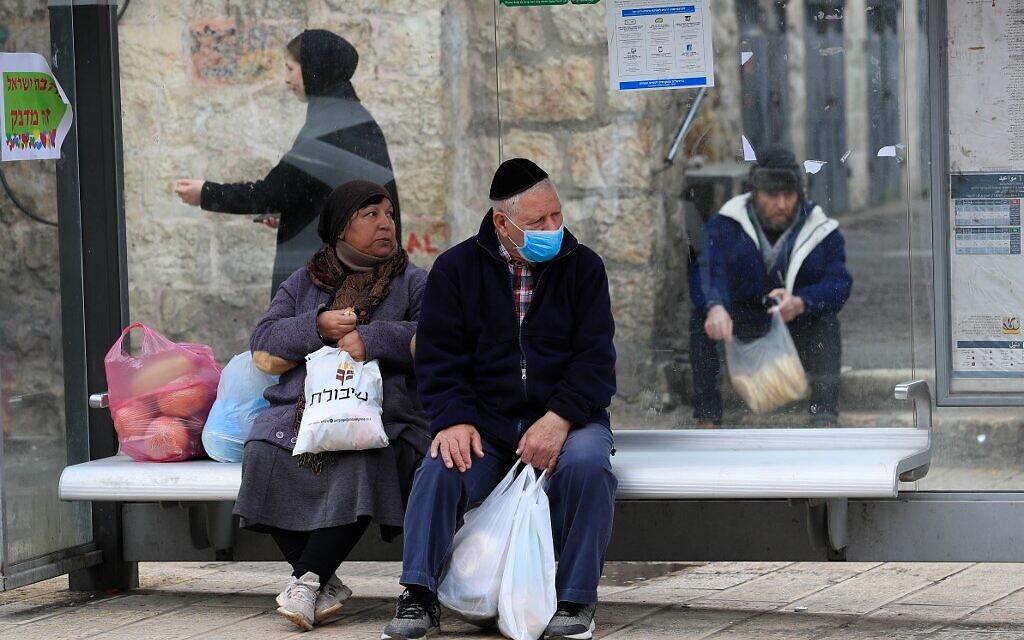 Un Israélien portant un masque attend un bus à Jérusalem le 19 mars 2020. (Crédit : EMMANUEL DUNAND / AFP)