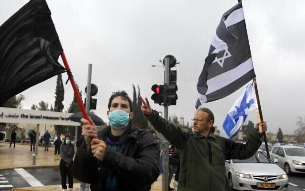 Les manifestants brandissent un drapeau noir, un drapeau israélien et un drapeau israélien aux couleurs inversées, devant la Knesset à Jérusalem, le 19 mars 2020. La manifestation s'opposait à la récente décision du président de la Knesset de fermer l'Institution pendant plusieurs jours, et contre ce qu'ils ont décrit comme des «dommages à la démocratie israélienne». (Crédit : MENAHEM KAHANA / AFP)