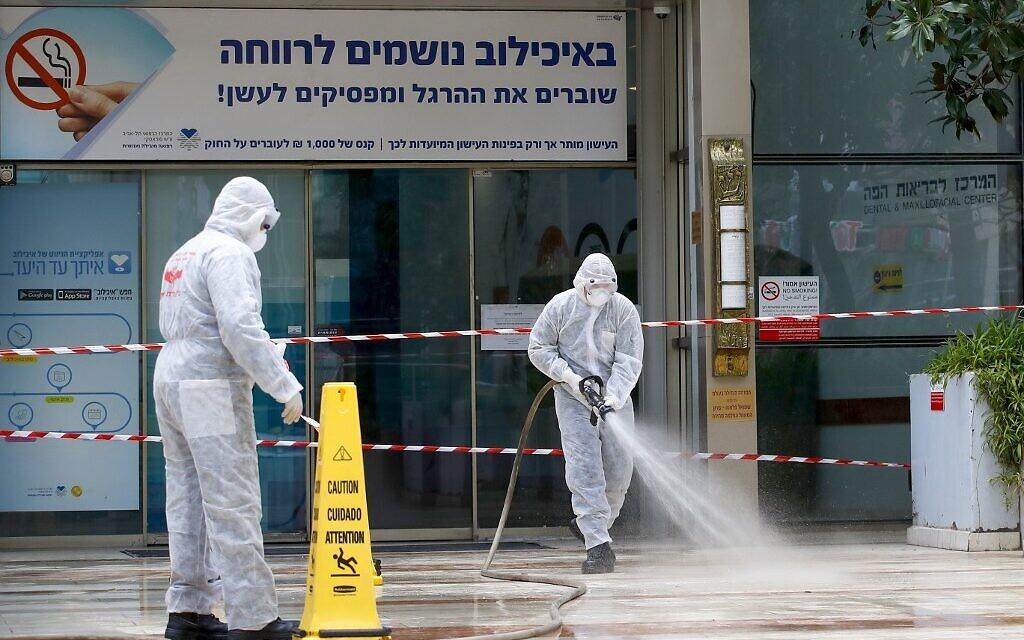 Un pompier israélien pulvérise du désinfectant à l'entrée du centre médical Sourasky de Tel-Aviv, le 20 mars 2020. (Crédit : JACK GUEZ / AFP)