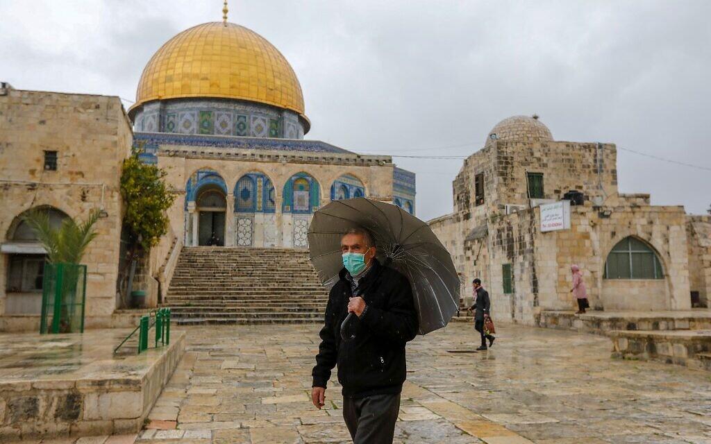 Un Palestinien portant un masque de protection contre le COVID-19, se trouve devant la mosquée du Dôme du Rocher dans l'enceinte presque déserte de la mosquée Al-Aqsa, dans la vieille ville de Jérusalem, le 20 mars 2020. (Crédit : AHMAD GHARABLI / AFP)
