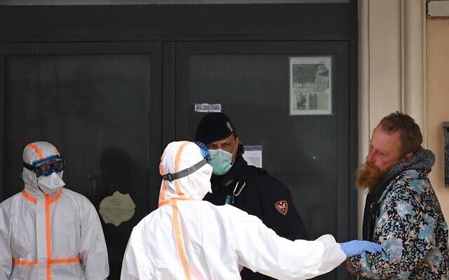 Des membres du personnel médical vêtus d'un uniforme de protection sauvent un sans-abri à Ostie, dans la banlieue de Rome, le 21 mars 2020(Crédit : Alberto PIZZOLI / AFP)