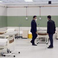 Du personnel iranien met en place un hôpital improvisé à l'intérieur d'un centre commercial iranien dans le nord ouest de Téhéran , le 21 mars 2020 en pleine crise du coronavirus. (Photo par STR / AFP)