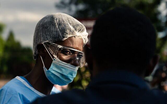 Un membre de l'hôpital Parirenyatwa Hospita contrôle les personnes et leur donne du désinfectant pour les mains avant qu'elles entrent dans l'hôpital alors que le pays tente de bloquer la propagation du coronavirus COVID-19 à Harare au Zimbabwe, le 23 mars 2020. (Photo par Jekesai NJIKIZANA / AFP)