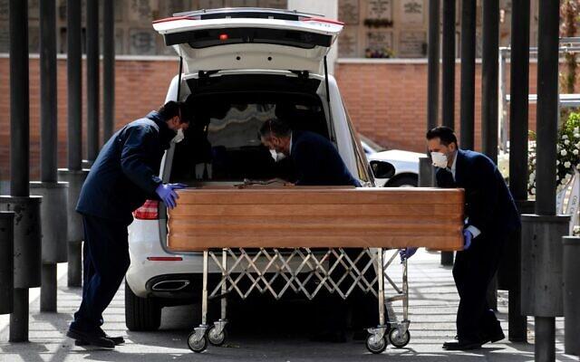 Des employés des pompes funèbres portant des masques transportent un cercueil vers le crématorium du cimetière de La Almudena à Madrid le 24 mars 2020 lors de l'enterrement d'une victime du coronavirus COVID-19. (Photo by OSCAR DEL POZO / AFP)