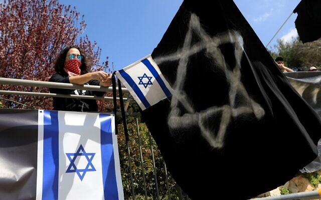 """Une femme israélienne participe à une manifestation """"pour sauver la démocratie israélienne"""" devant la Knesset à Jérusalem, le 25 mars 2020. (Emmanuel DUNAND / AFP)"""