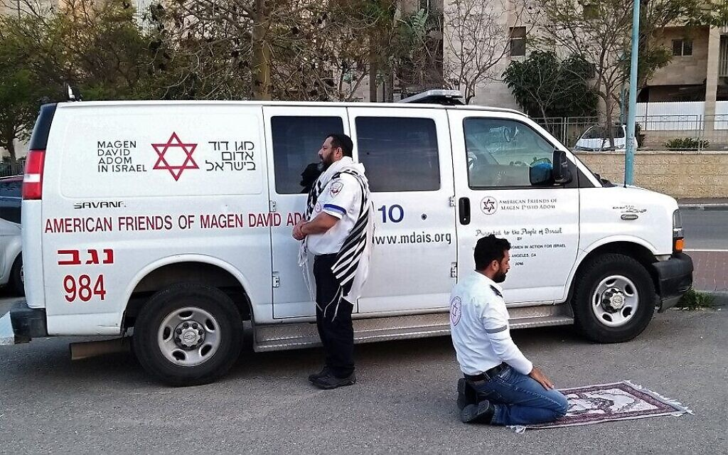Deux ambulanciers priant devant une ambulance des American Friends of Magen David Adom (AFMDA) : un Juif de Beer Sheva face à Jérusalem, et un Arabe de Rahat face à la Mecque, le 24 mars 2020. (Crédit : MAGEN DAVID ADOM)
