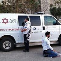 Deux ambulanciers priant devant une ambulance des American Friends of Magen David Adom (AFMDA) : un juif de Beersheba face à Jérusalem, et un arabe de Rahat face à la Mecque, le 24 mars 2020. (Crédit : MAGEN DAVID ADOM)