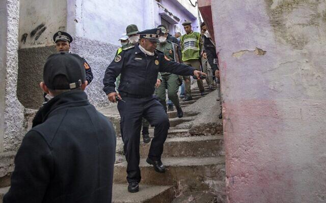 Dans le cadre d'une patrouille commune des forces de sécurité, un policier marocain donne l'instruction à un homme de rester chez lui comme mesure de protection  contre l'épidémie de COVID-19 dans le quartier de Takadoum de la capitale Rabat, le 27 mars 2020. (Photo par FADEL SENNA / AFP)
