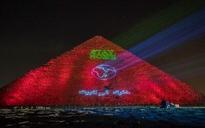 Spectacle lumineux sur la pyramide de Guizeh appelant le monde à se confiner, en pleine pandémie de coronavirus, le 30 mars 2020. (Crédit : Khaled DESOUKI / AFP)