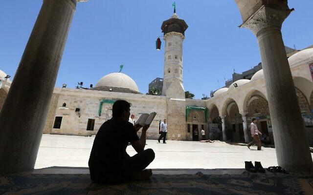 Un Palestinien lit un exemplaire du Coran, le livre saint de l'Islam, dans une mosquée le premier jour du mois de jeûne sacré du Ramadan dans la ville de Gaza, le 18 juin 2015. (PHOTO AFP/MAHMUD HAMS)