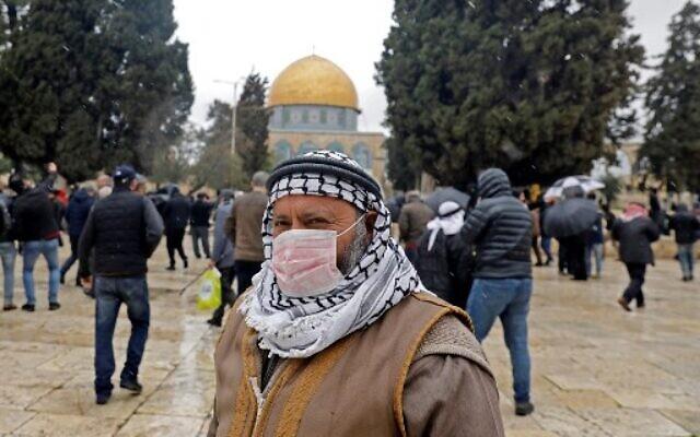 Un Palestinien portant un masque de protection comme mesure de protection contre le coronavirus se tient devant la mosquée du Dôme du Rocher sur le mont du Temple, dans la vieille ville de Jérusalem, avant les prières du vendredi, le 6 mars 2020. (Crédit : Ahmad Gharabli / AFP)