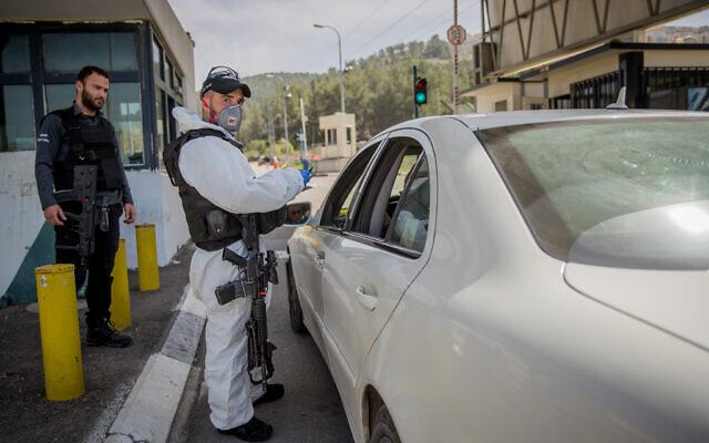 Un membre de la police des frontières israélienne porte un équipement de protection et un masque contre le coronavirus, au point de contrôle d'Ein Yael, près du zoo biblique de Jérusalem, le 11 mars 2020. (Crédit : Yonatan Sindel / Flash90)