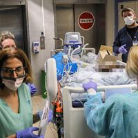 Des membres du personnel de l'hôpital Ichilov de Tel Aviv déplacent un patient vers un nouveau service, le 22 mars 2020. (Crédit : Yossi Zamir / Flash90)