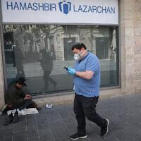 Un homme portant un masque pour se protéger du coronavirus, devant un sans-abri, près d'un centre commercial fermé à Jérusalem, le 23 mars 2020. (Crédit : Olivier Fitoussi / Flash90)