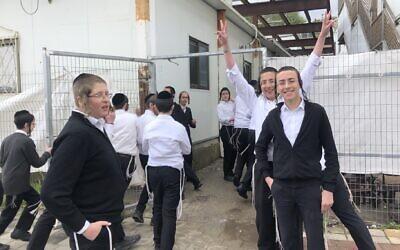 Quelques-uns des élèves d'une école de garçons haredi à Ramat Beit Shemesh Bet, à l'ouest de Jérusalem, où les cours ont toujours lieu, le 18 mars 2020. (Crédit : Sam Sokol/JTA)