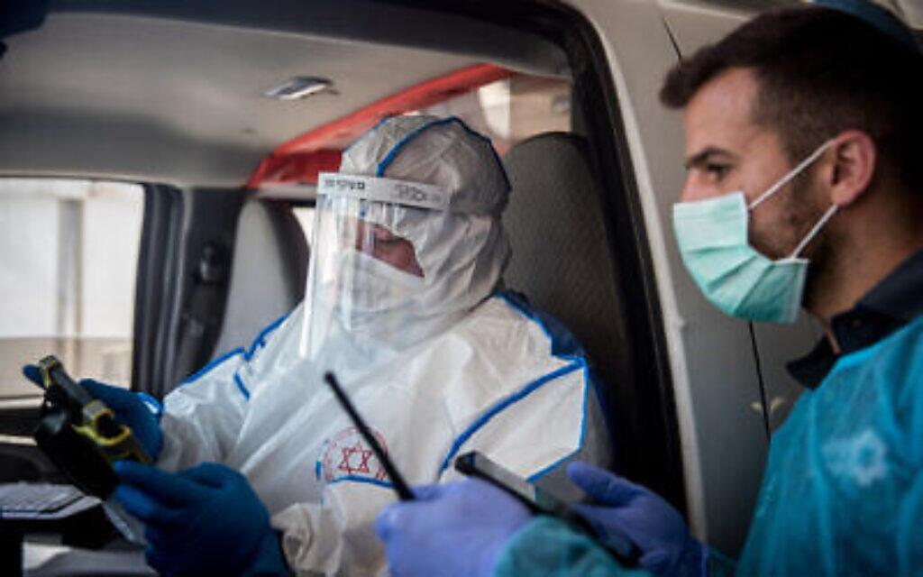 Des ambulanciers du service d'urgence du Magen David Adom portant des vêtements de protection à titre préventif contre le coronavirus conduisent une femme soupçonnée d'être porteuse du coronavirus au centre médical Shaare Zedek de Jérusalem, le 24 mars 2020. (Crédit : Yonatan Sindel / Flash90)