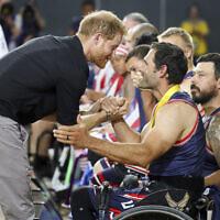 Le prince Harry de Grande-Bretagne félicite un membre de l'équipe américaine de basket-ball en fauteuil roulant après avoir remporté la médaille d'or lors de la huitième journée des Invictus Games à Sydney, en Australie, le 27 octobre 2018. (Crédit : Chris Jackson/Pool Photo via AP)