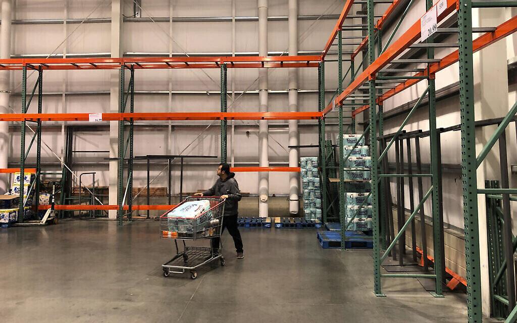 Un client passe devant des rayons principalement vides et normalement remplis de papier toilette et de serviettes en papier dans un magasin Costco à Teterboro, dans le New Jersey. (Crédit : AP Photo/Seth Wenig)
