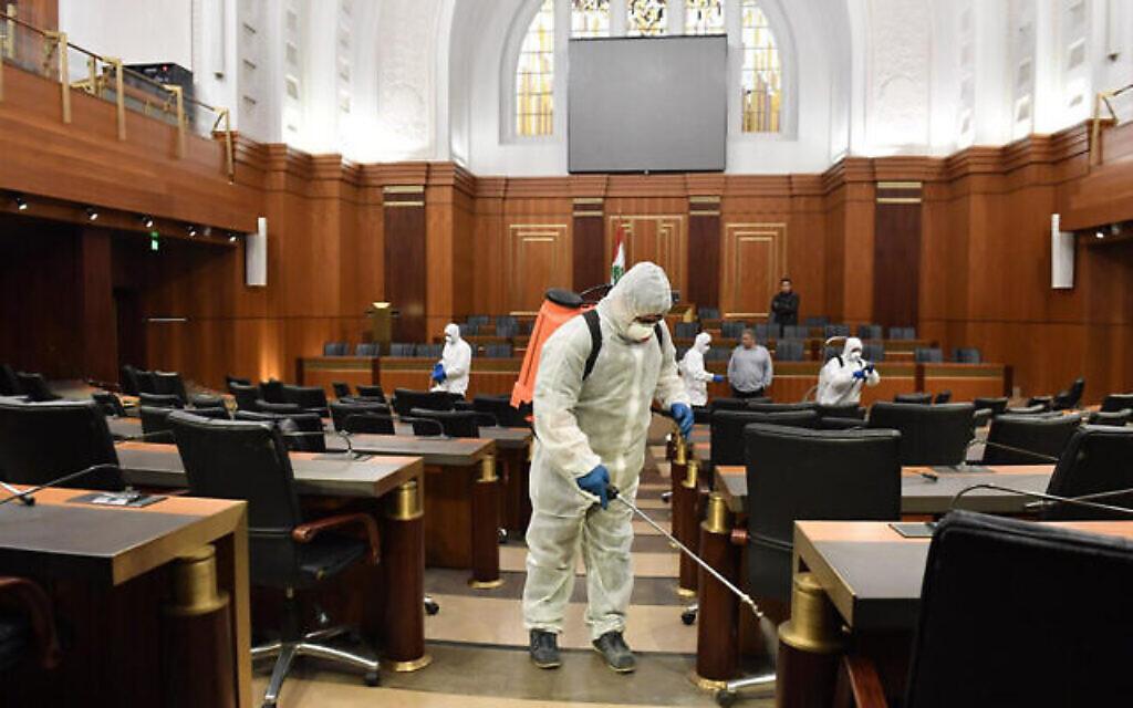 Des agent en tenue de protection désinfectent par précaution le hall principal du Parlement libanais, à Beyrouth, le 10 mars 2020. (Crédit : AP Photo / Ali Fawaz, Bureau médiatique du Parlement libanais)