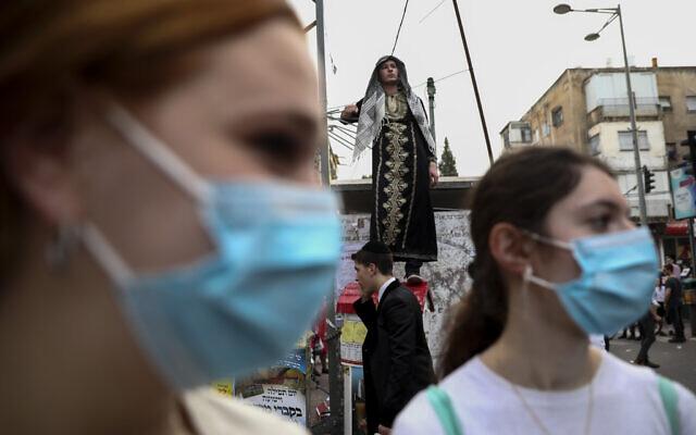 Des filles portent des masques pendant les célébrations de la fête juive de Pourim à Bnei Brak, Israël, le 10 mars 2020. (Crédit : AP Photo/Oded Balilty)