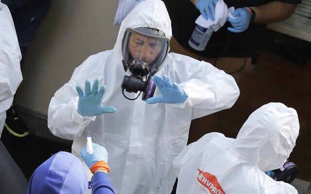 Les agents de nettoyage de Servpro sont aspergés à la sortie du Life Care Center de Kirkland, Washington, le 12 mars 2020. (Crédit : AP Photo/Ted S. Warren)