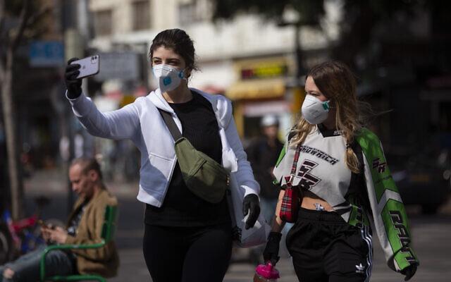 Deux femmes portant un masque de protection prennent un selfie à Tel Aviv, le 15 mars 2020. (Crédit : AP Photo/Oded Balilty)
