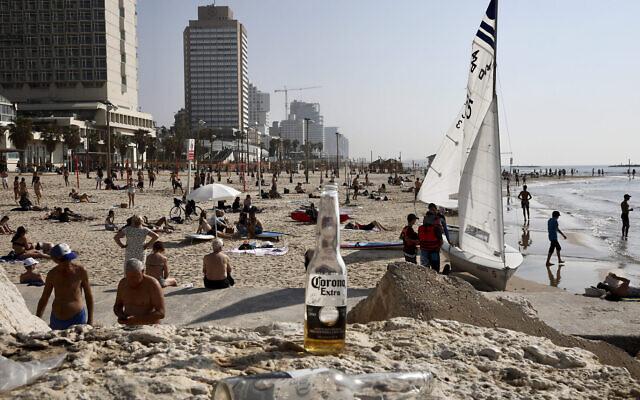 En pleine pandémie de coronavirus, les Israéliens envahissent les plages de Tel Aviv, le 17 mars 2020. (Crédit : AP Photo/Oded Balilty)