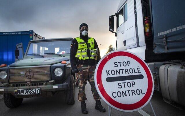 Illustration : Un garde-frontière lituanien se tient à côté de camions bloqués dans les embouteillages sur 60 kilomètres à la frontière lituanienne pour entrer en Pologne, le mardi 17 mars 2020. (AP Photo/Mindaugas Kulbis)