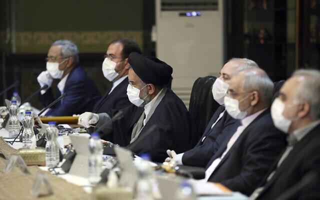 Sur cette photo publiée par le site internet officiel du Bureau de la présidence iranienne, des membres du cabinet portant des masques et des gants participent à une réunion à Téhéran, en Iran, le mercredi 18 mars 2020. (Bureau de la présidence iranienne via AP)