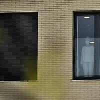 Une gemme portant un masque de protection à la fenêtre de la maison de retraite de San Martin où plusieurs personnes âgées sont touchées par le coronavirus à Vitoria, dans le nord de l'Espagne, le 19 mars 2020 (Crédit :  AP Photo/Alvaro Barrientos)