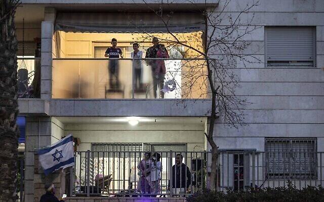 Les habitants de Jérusalem sur leurs balcons, applaudissent les soignants mobilisés pour la lutte contre le coronavirus, le 19 mars 2020. (Crédit : AP Photo/Tsafrir Abayov)
