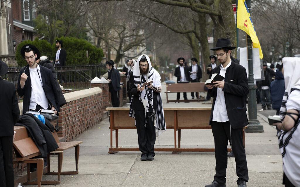 """Des Juifs orthodoxes appliquent la directive de """"distanciation sociale"""" lors d'une prière aux abords du siège mondial du mouvement Habad Loubavitch à Brooklyn, à New York, le 20 mars 2020. (Crédit : AP Photo/Mark Lennihan)"""