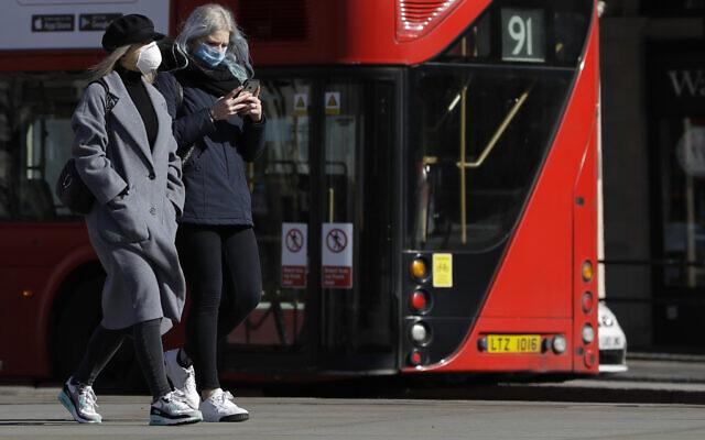 Deux femmes portent des masques de protection en pleine pandémie de coronavirus, à Londres, le 22 mars 2020. (Crédit : AP Photo/Kirsty Wigglesworth)