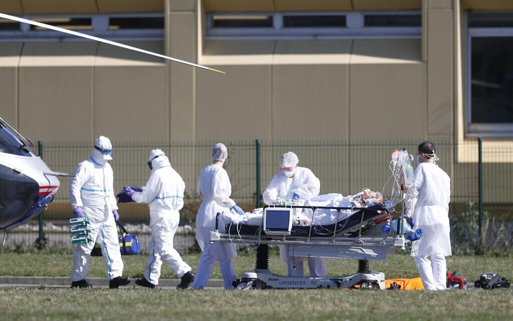 Une victime du virus Covid-19 est évacuée de l'hôpital civil de Mulhouse, dans l'est de la France, le lundi 23 mars 2020. (Crédit : AP Photo/Jean-Francois Badias)