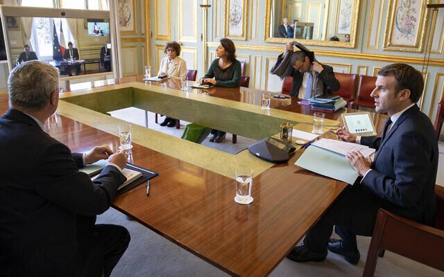 Le président français Emmanuel Macron, en vidéoconférence avec les représentants des cultes, au palais de l'Elysée, le 23 mars 2020. (Crédit :Ian Langsdon, Pool via AP)