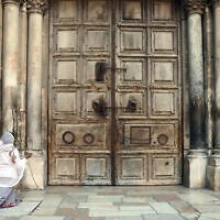 Une femme prie devant l'église fermée du Saint-Sépulcre, dans la Vieille Ville de Jérusalem, le 25 mars 2020. (Mahmoud Illean/AP)