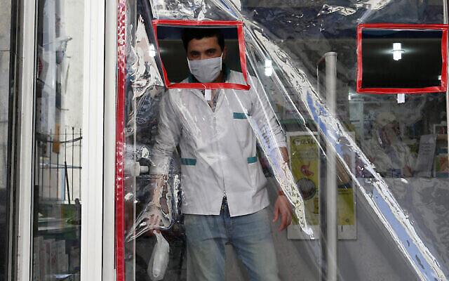 Un pharmacien porte un masque derrière une porte recouverte de plastique pour éviter la contamination, à Casablanca, Maroc, le 27 mars 2020. (AP Photo/Abdeljalil Bounhar)