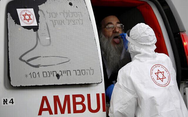 Un personnel soignant portant une combinaison de protection prélève un échantillon sur un Juif ultra-orthodoxe pour un test au coronavirus à Bnei Brak, le 31 mars 2020 (Crédit : AP Photo/Ariel Schalit)