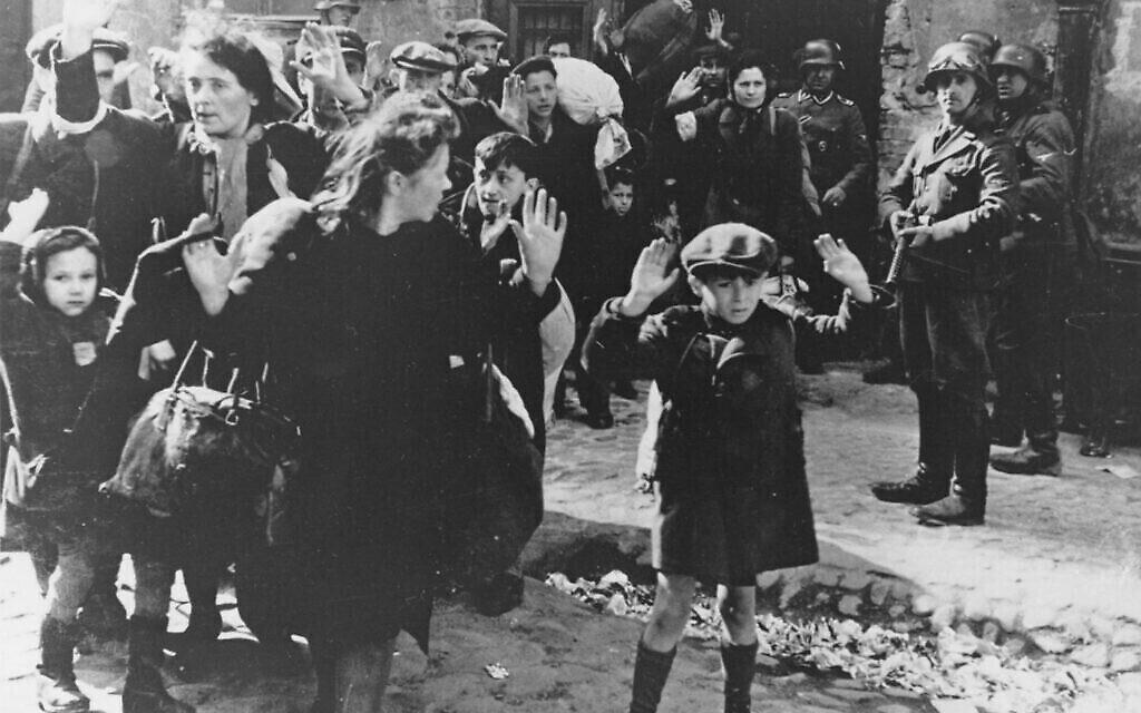 Un groupe de Juifs, dont un petit garçon, est escorté hors du ghetto de Varsovie par des soldats allemands, 19 avril 1943. (AP Photo)