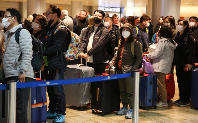 Illustration : des touristes sud-coréens portant des masques afin de se protéger du coronavirus à l'aéroport international Ben Gurion, le 24 février 2020. (Crédit : Flash90)