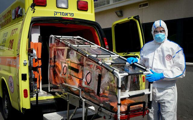 Un employé du Magen David Adom avec son équipement de protection contre le coronavirus, aux abords du centre d'appel d'urgence de Kiryat Ono, le 26 février 2020 (Crédit :  Flash90)