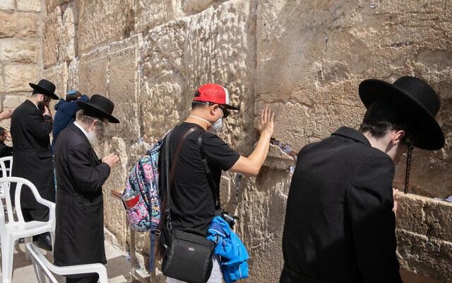 Un touriste portant un masque facial par crainte du coronavirus, prie au mur Occidental dans la Vieille Ville de Jérusalem, le 27 février 2020. (Olivier Fitoussi/Flash90)