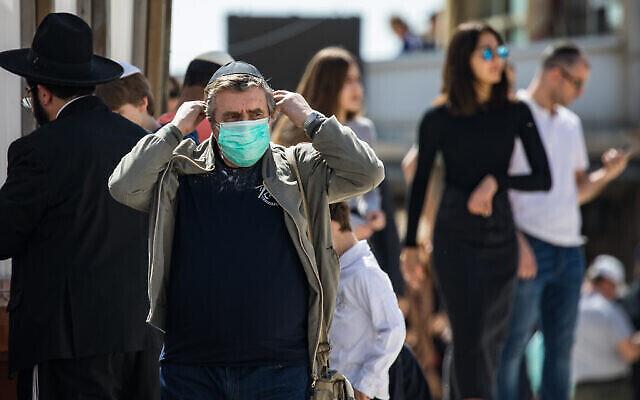 Un touriste portant un masque pour se protéger du coronavirus au mur Occidental, dans la Vieille Ville de Jérusalem, le 5 mars 2020. (Crédit : Olivier Fitoussi / Flash90)