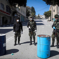 Les forces de sécurité palestiniennes portant des masques bloquent l'entrée de la ville de Bethléem en Cisjordanie, le 8 mars 2020. (Wisam Hashlamoun/Flash90)