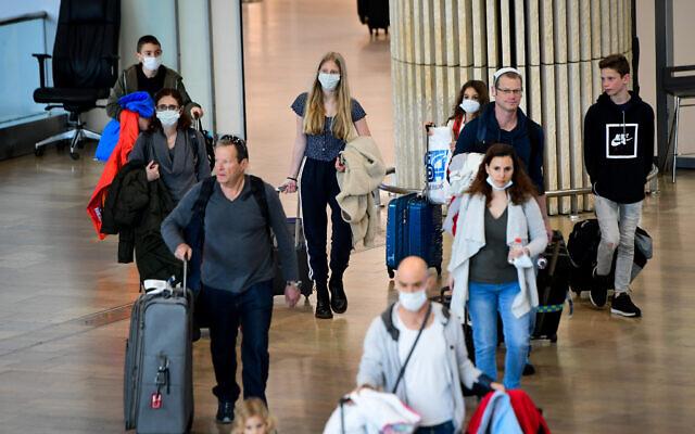 Des personnes portant des masques de protection par crainte du coronavirus arrivent à l'aéroport international Ben Gurion, le 10 mars 2020. (Avshalom Sassoni/Flash90)
