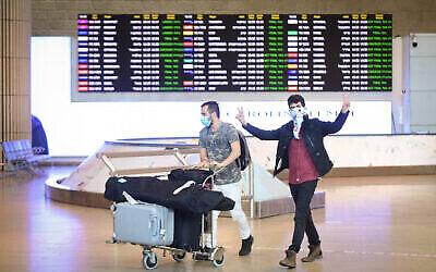 Des personnes portant un masque facial arrivent à l'aéroport international Ben Gurion, le 11 mars 2020. (Flash90)