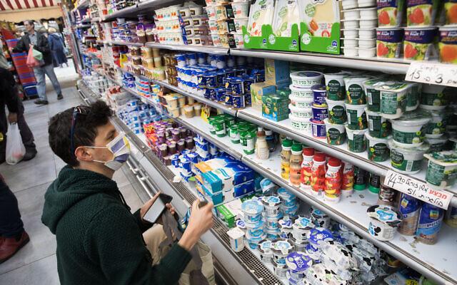 Un homme porte un masque pour se protéger du coronavirus en faisant des courses dans un supermarché de Jérusalem le 15 mars 2020. (Crédit : Nati Shohat/Flash90)