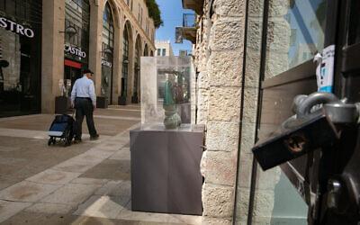 Un homme passe devant un magasin Castro fermé au Mamila Mall de Jérusalem, vide, le 16 mars 2020 (Crédit : Olivier Fitoussi/Flash90)